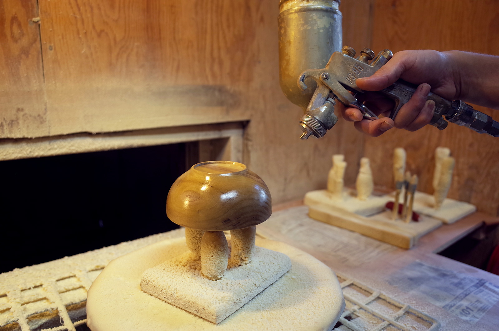 器を回転させながら全体に塗料を吹き付ける様子